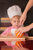 little cute kid in a cook cap playing in the