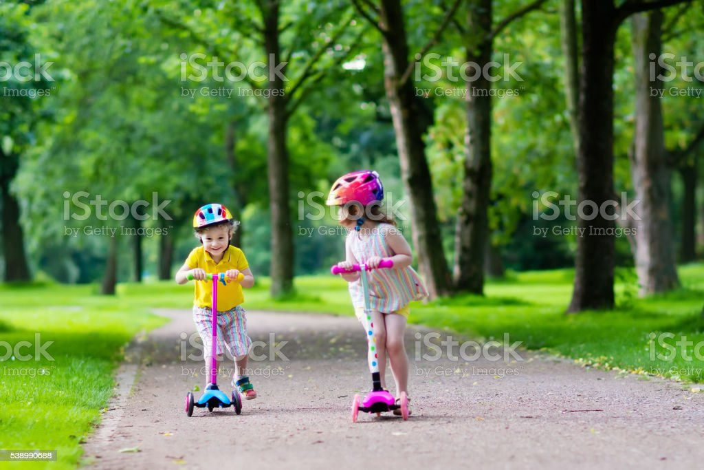 Little cute kids riding colorful scooters stock photo