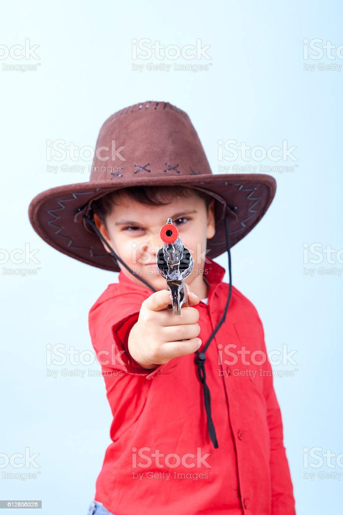 Little Dangerous Cowboy is Pointing His Toy Gun Against Blue stock photo