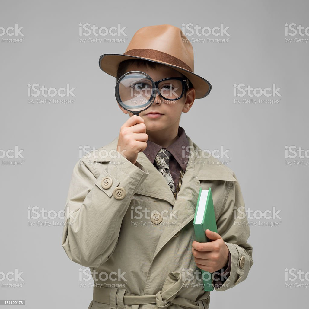 Little dedective looking through magnifying glass on gray background stock photo