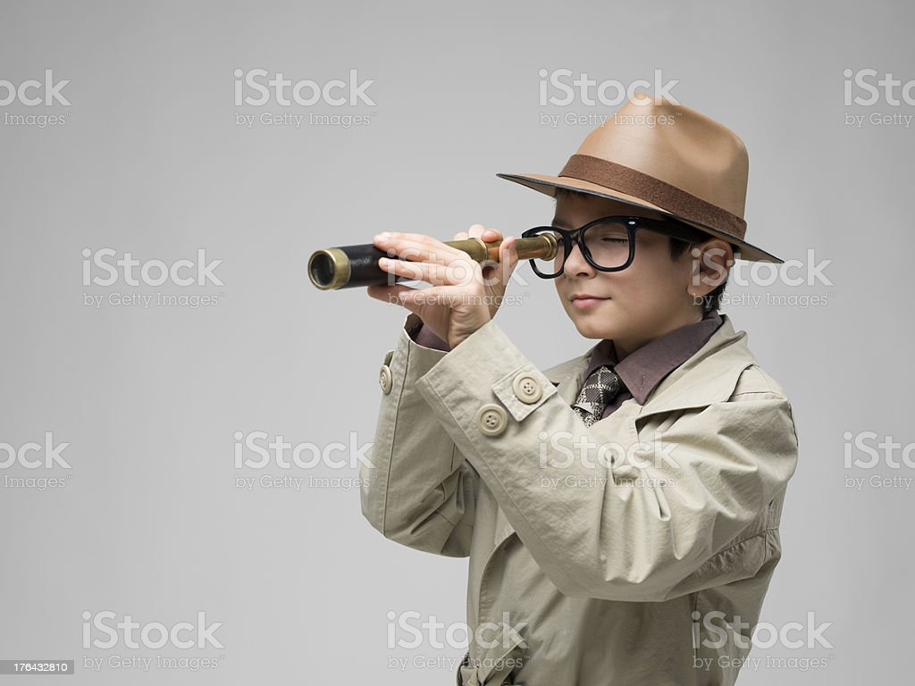 Little detective in trench coat holding hand held telescope royalty-free stock photo