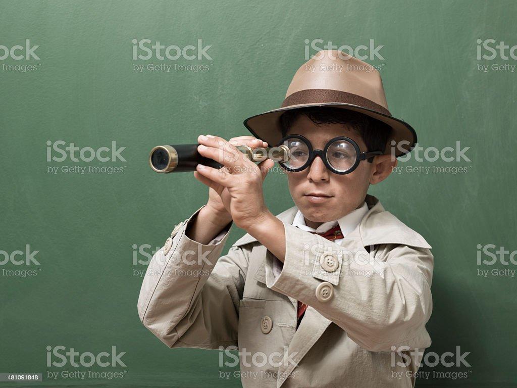 Little detective looking through hand held telescope on green blackboard stock photo