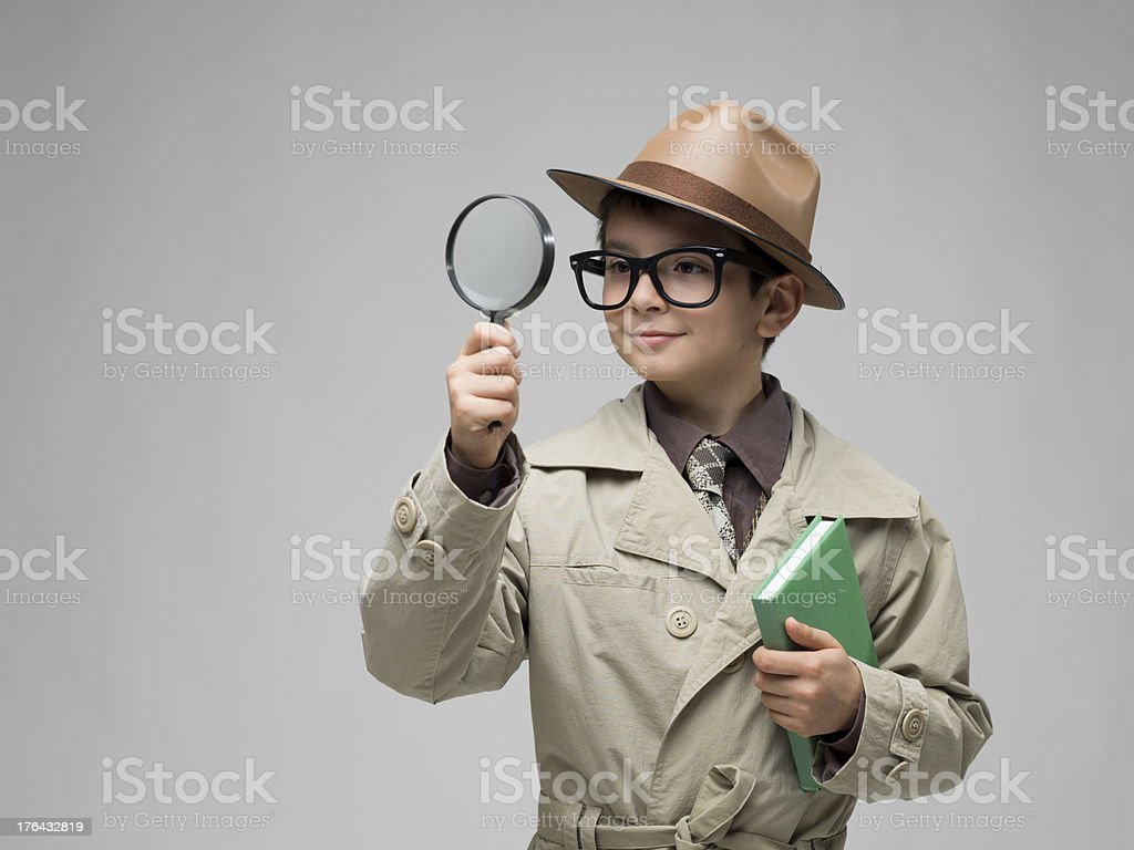 Little detective looking through magnifying glass on gray background stock photo