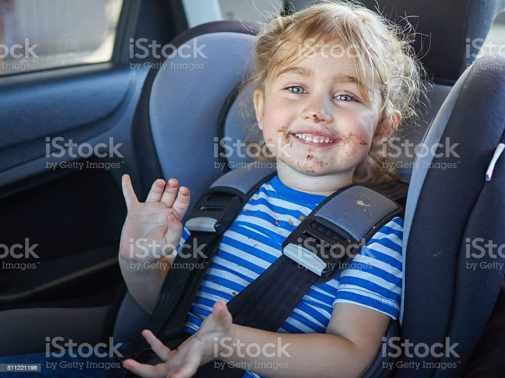 Little dirty girl , baby in a safety car seat. stock photo