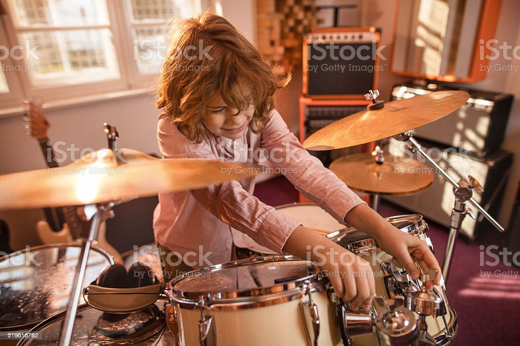 Little drummer adjusting drum kit in music studio. stock photo