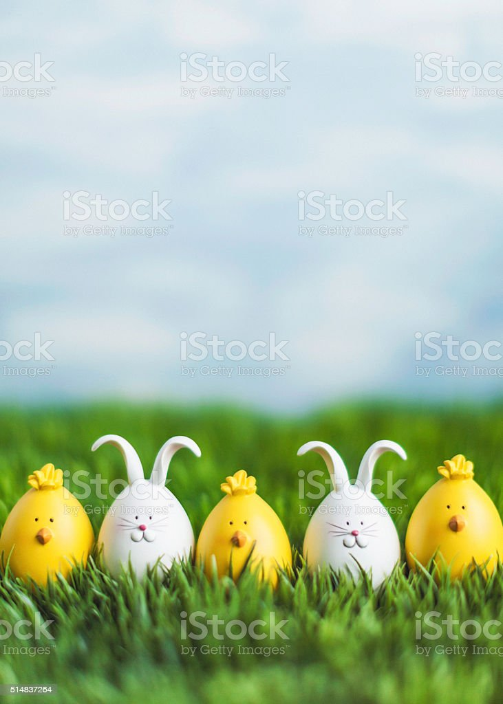 Little Easter critters sitting in grass with big blue sky stock photo
