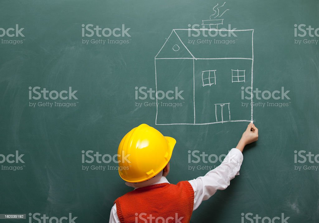 Little engineer with helmet drawing a house on blackboard royalty-free stock photo