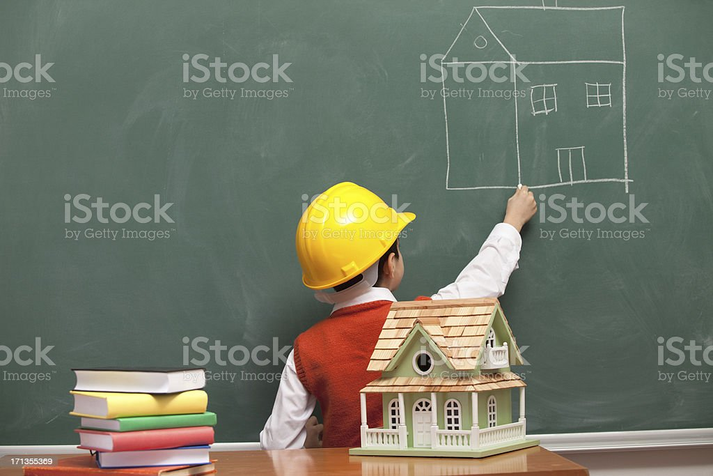 Little engineer with helmet drawing house on blackboard royalty-free stock photo