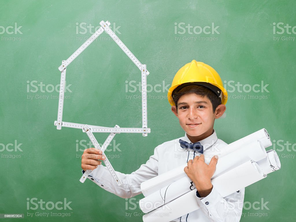 Little engineer with helmet holding blue prints and ruler stock photo
