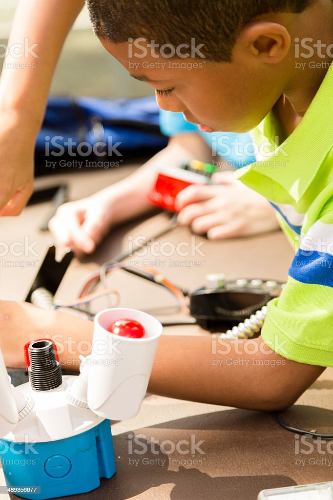 Little engineers!  Elementary children collaborate on 'robot' they created. stock photo