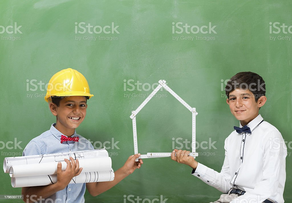 Little engineers holding folding ruler in house shape royalty-free stock photo