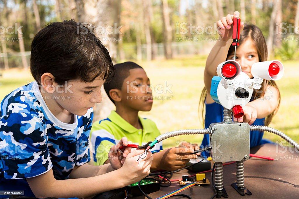 Little engineers! Multi-ethnic elementary children collaborate on 'robot' creation. stock photo