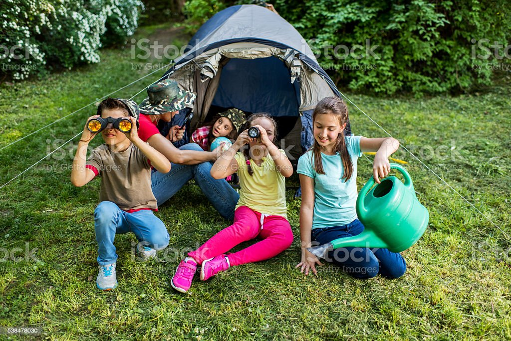 Little explorers with a teacher on a camping in nature. stock photo