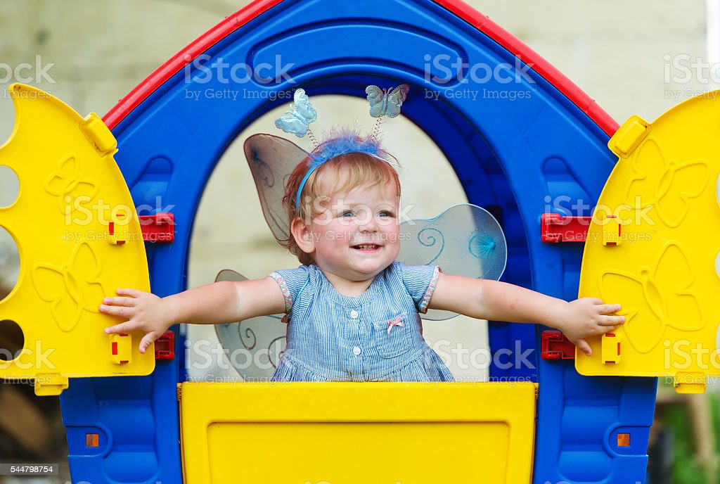 Little fairy with wings looks out of children's lodge. stock photo