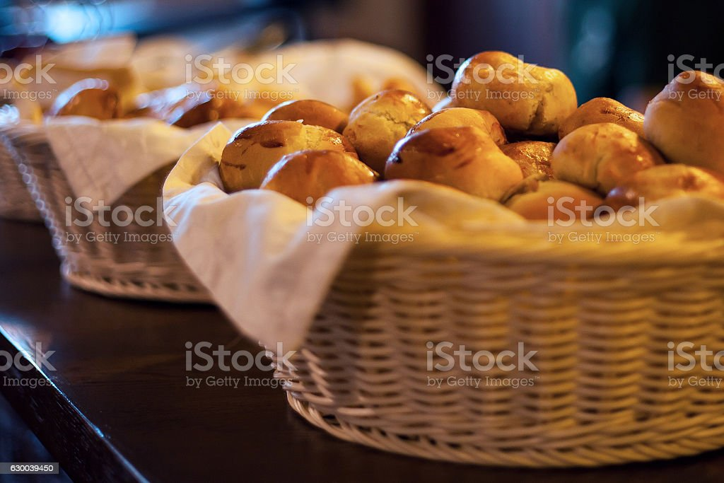 little fresh buns in basket on table stock photo
