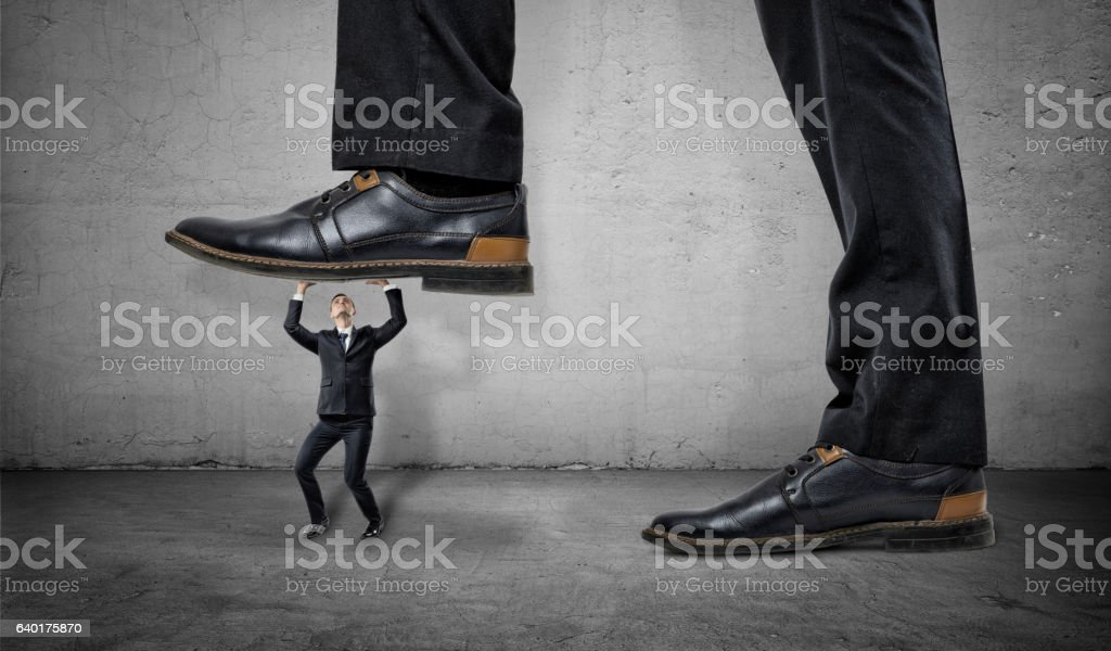 Little frightened worker under feet of huge businessman on grey stock photo