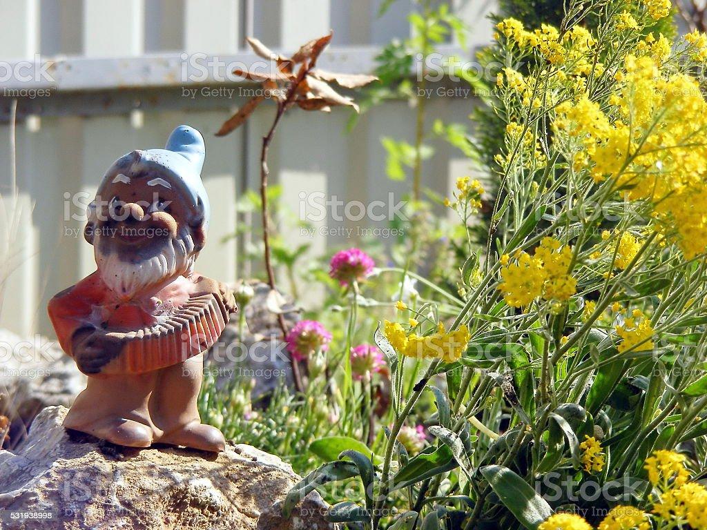 Little garden gnome in the rockery stock photo
