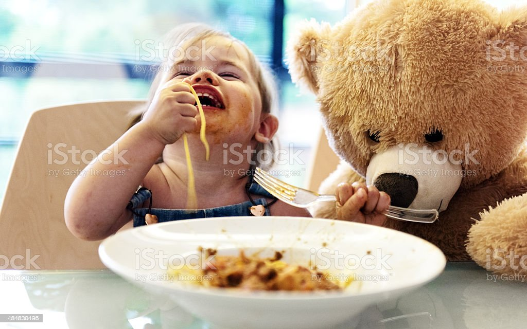 Little girl 2 years old girl eating noodles stock photo