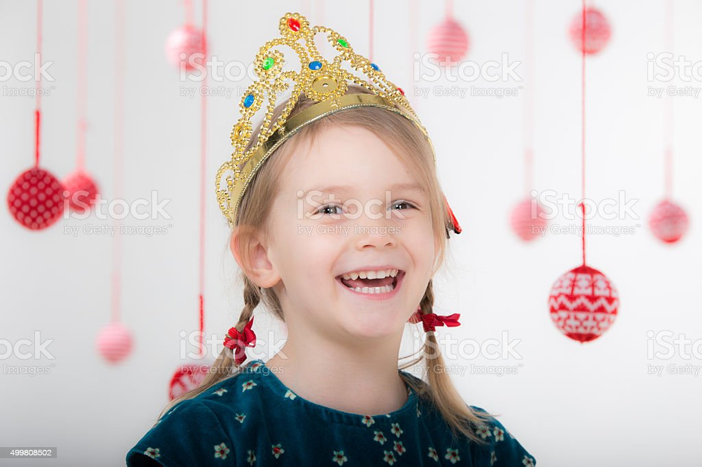 little girl, a crown on his head, laughing merrily stock photo