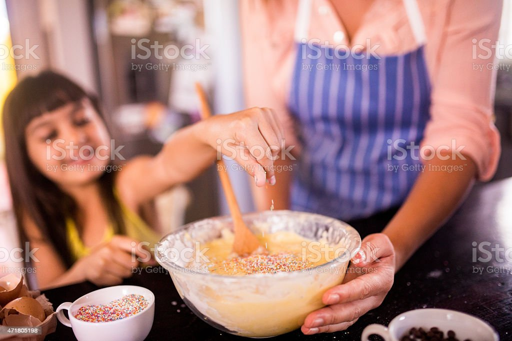 Little girl adding sprinkles to the cake mix stock photo