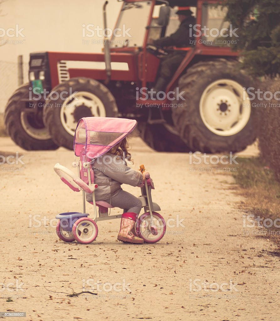 Little girl against big tractor stock photo