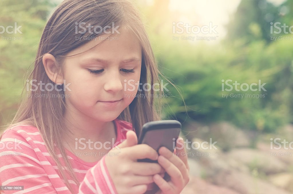 Little girl and a smart phone stock photo