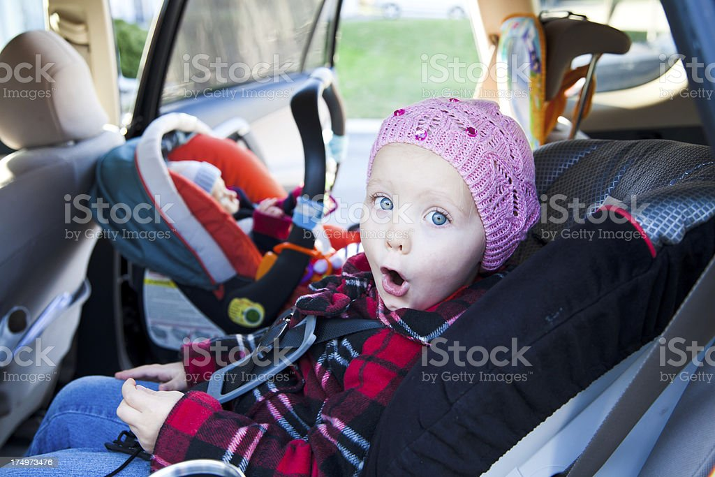 Little girl and baby boy sitting in car seats stock photo