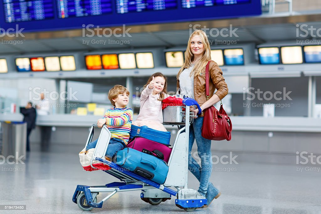 Little girl and boy and mother with suitcases on airport stock photo