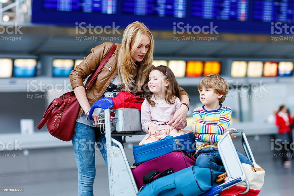 Little girl and boy and young mother with suitcases stock photo