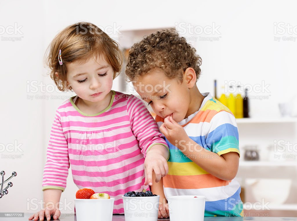 Little Girl And Boy Eating Fruit In the Kitchen stock photo