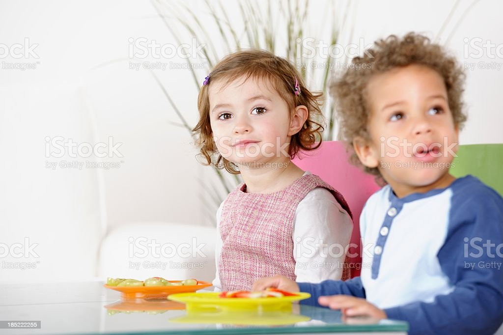 Little Girl and Boy Eating Fruit In The Living Room stock photo