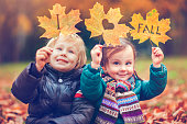 Little girl and boy happy in autumn park