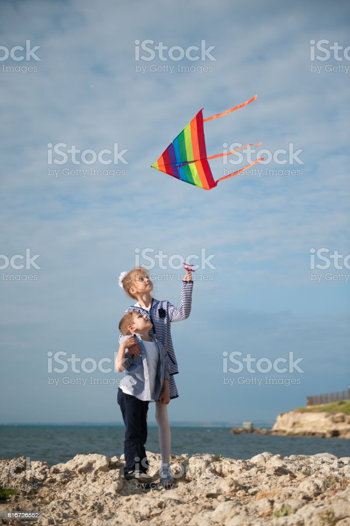 little girl and boy hold flying kite while standing on a cliff against the sea stock photo