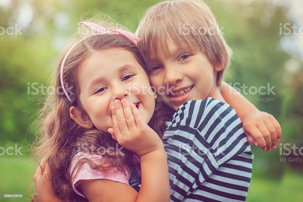 Little girl and boy hugging stock photo