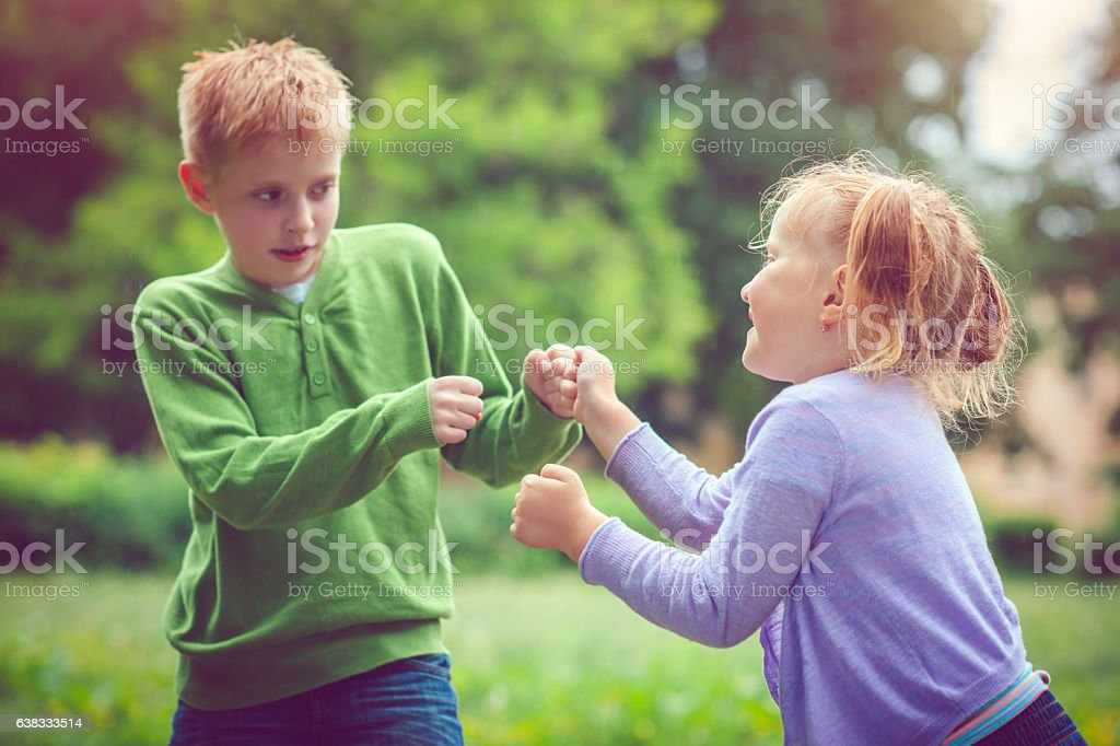Little girl and boy in conflict stock photo