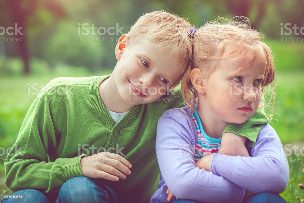 Little girl and boy outdoors stock photo