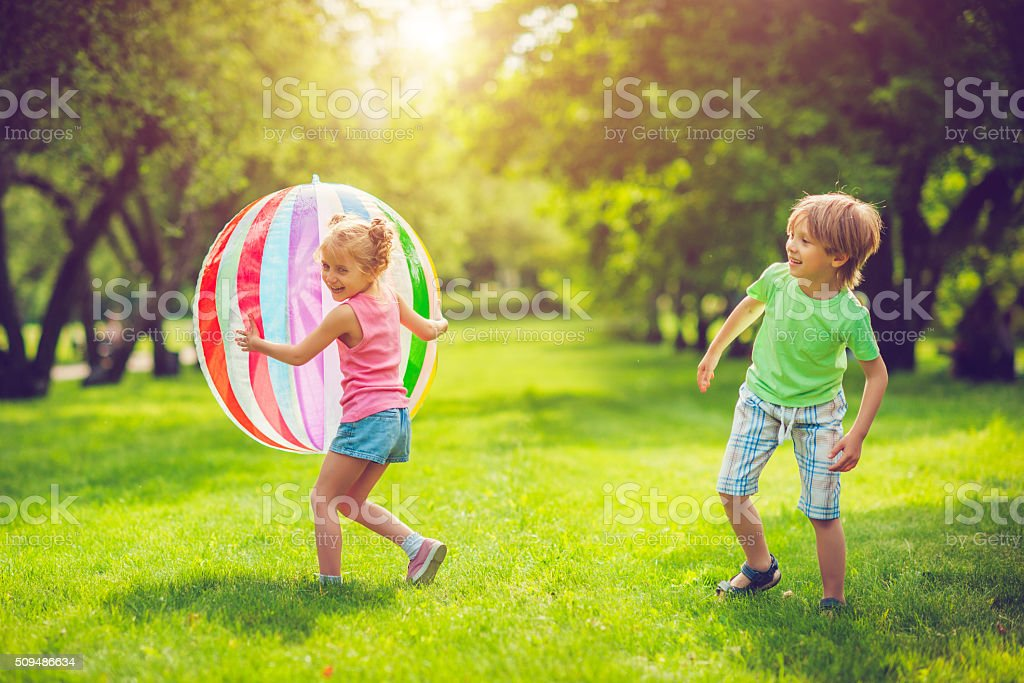 Little girl and boy playing with ball stock photo