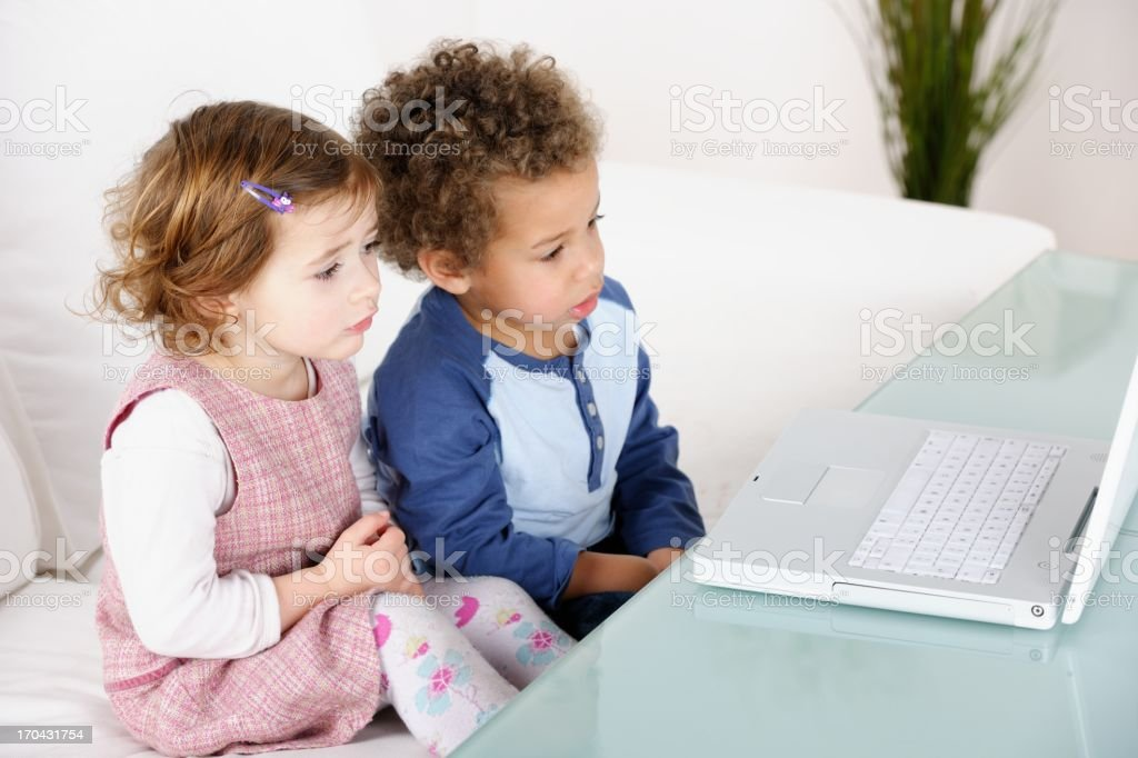 Little Girl And Boy Using Computer In The Sitting Room stock photo