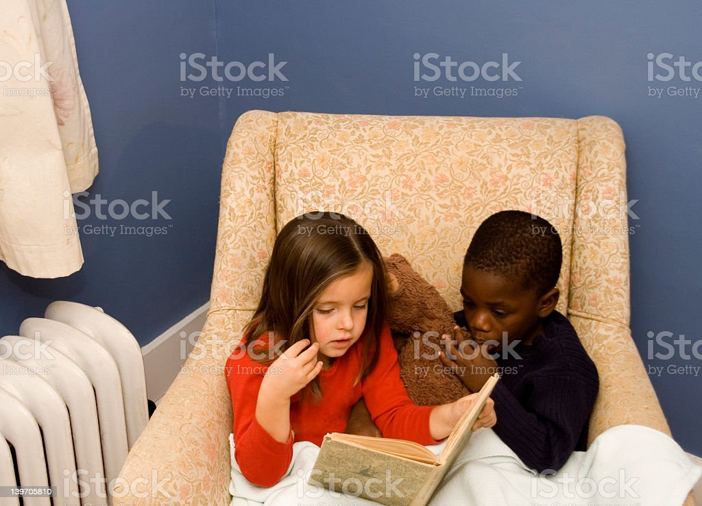 A little girl and boy with a teddy bear enjoying story time royalty-free stock photo