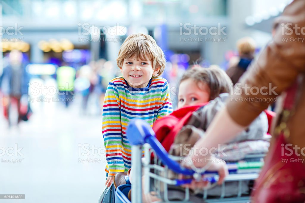 Little girl and boy, young mother with suitcases on airport stock photo