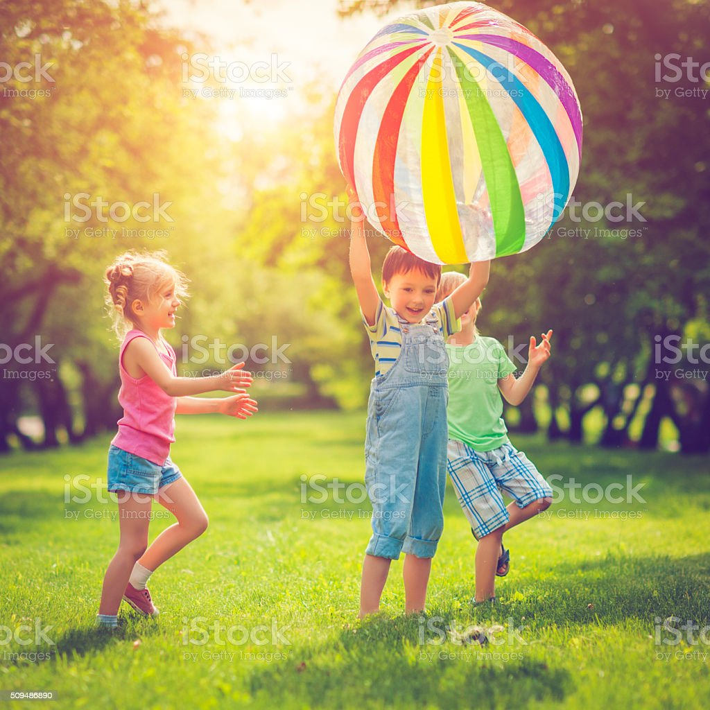 Little girl and boys playing with ball stock photo