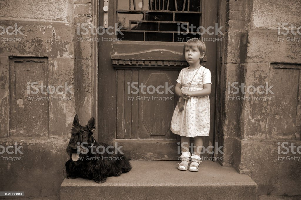 Little girl and dog in front of old house. royalty-free stock photo