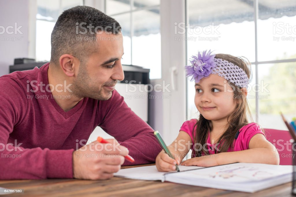 Little Girl And Father Drawing Pictures Together stock photo