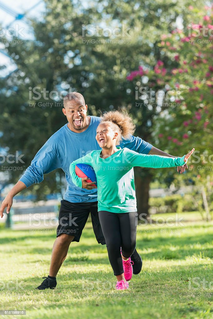 Little girl and father playing in the park with ball stock photo