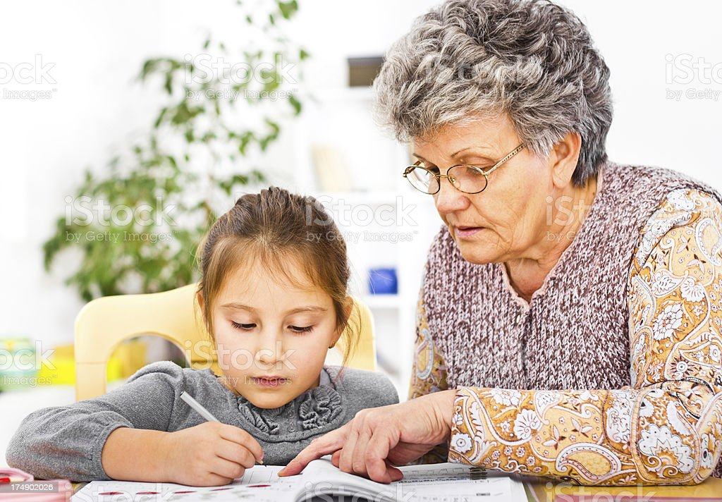 Little girl and grandmother learning royalty-free stock photo