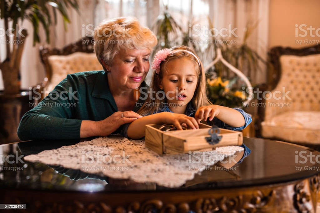 Little girl and grandmother looking at jewelry box at home. stock photo
