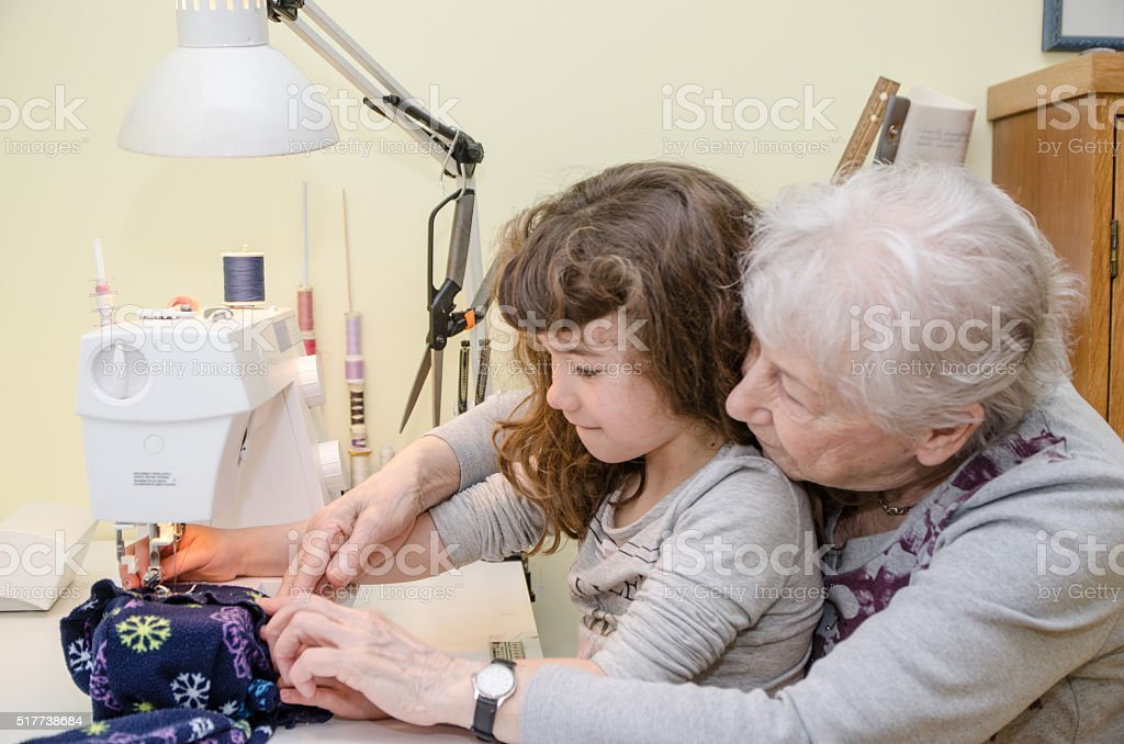 Little girl and grandmother on sewing machine stock photo