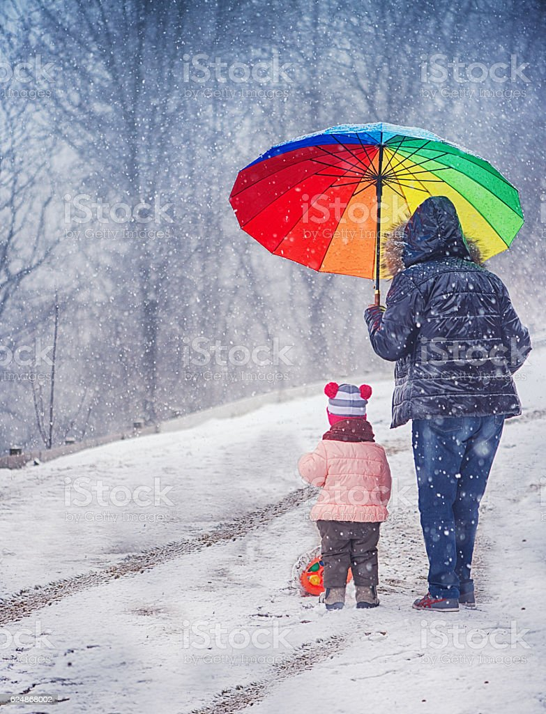 Little Girl and Grandmother With Umbrella in the Winter stock photo
