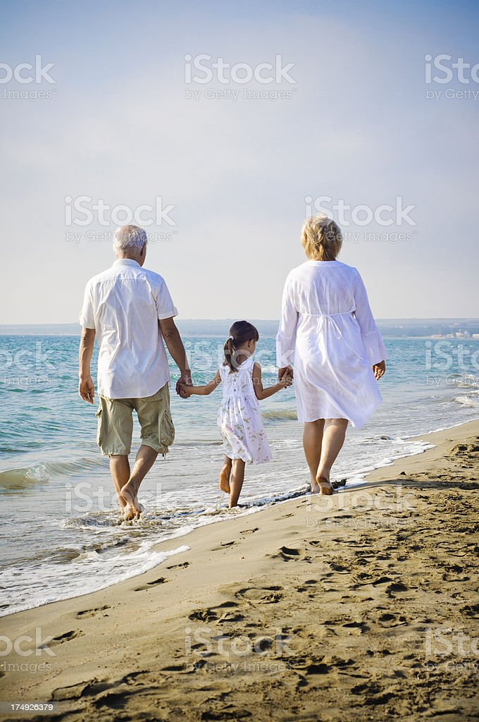 Little girl and her grandparents walking on the beach royalty-free stock photo