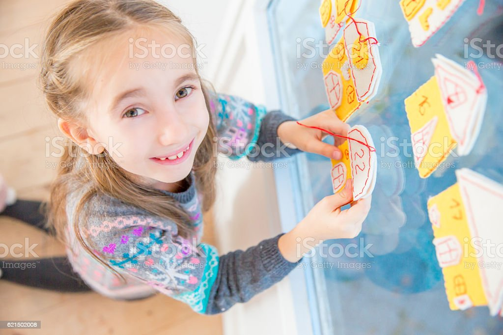 Little Girl and her Homemade Advent Calendar on Window stock photo